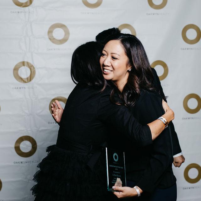 Oakwynite of the year Celine Bacani hugs Morgan Browne at the Oakwyn Sales Kickoff 2020